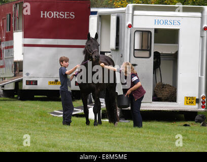 Mother and son washing down a horse after a ride, Chettle, Dorset, UK - Stock Image