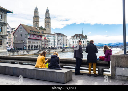 Zurich, Switzerland - March 2017: Young students people enjoying the view of river Limmat and Grossmünster church on Town Hall Bridge Rathausbrücke,   - Stock Image