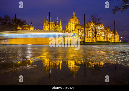 Budapest, Hungary - Illuminated Parliament of Hungary at blue hour with reflection and traditional yellow tram on the move - Stock Image