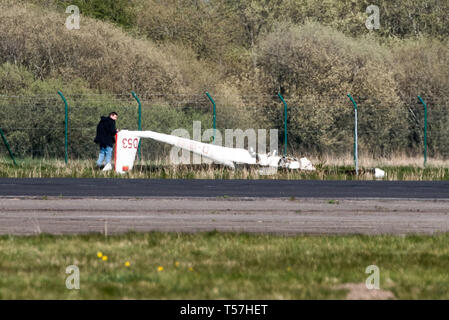 Leck, Germany. 22nd Apr, 2019. A crashed glider is lying on its back at the former military airfield in Leck. According to the fire department, the pilot died in the accident. (Best possible available quality) Credit: Benjamin Nolte/dpa - ATTENTION: Indicator(s) was (were) pixelated for legal reasons/dpa/Alamy Live News - Stock Image