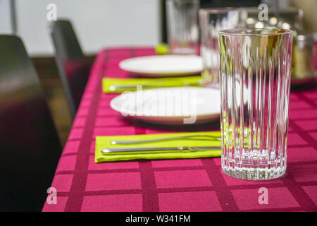 White plate, glass, fork and knife on a napkin. Red tablecloth - Stock Image
