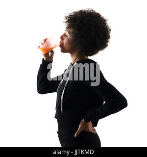 one mixed race african young teenager girl woman drinking orange juice  in studio shadow silhouette isolated on - Stock Image
