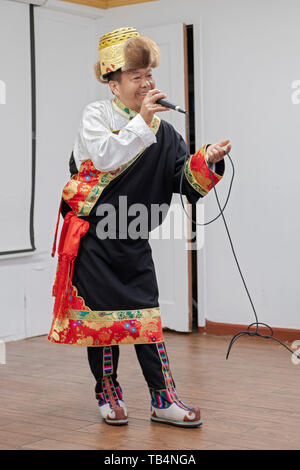 A Nepalese Buddhist man in a traditional costume sings Himalayan songs to seniors at the Sherpa Temple in Elmhurst, Queens, New York City. - Stock Image