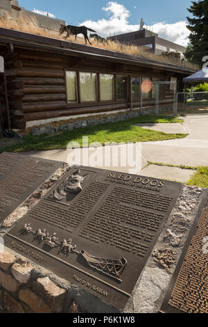 A plaque dedicated to Sled Dogs outside the Yukon Quest Dog Sled Race headquarters in Golden Heart Plaza downtown Fairbanks, Alaska. The 1,000-mile-long Yukon Quest International Sled Dog Race starts each year in the park. - Stock Image