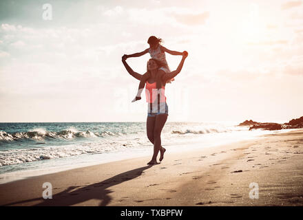 Mother and daughter running together along the seashore on the beach - Happy family piggyback at sunset - Stock Image