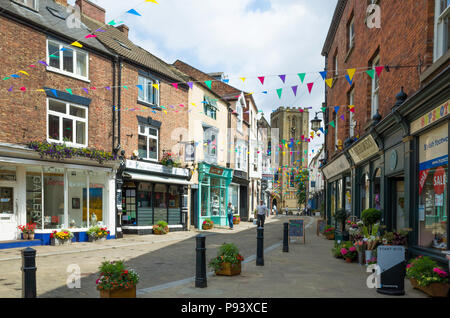 A view down Kirkgate towards the  west face of Ripon Cathedral North, Yorkshire, UK, on a sunny summer day - Stock Image