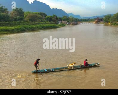 River in Vang Vieng Laos with people ferrying dogs over river - Stock Image