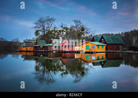 Tata, Hungary - Wooden fishing cottages on a small island at lake Derito (Derito to) in November at blue hour with reflection - Stock Image