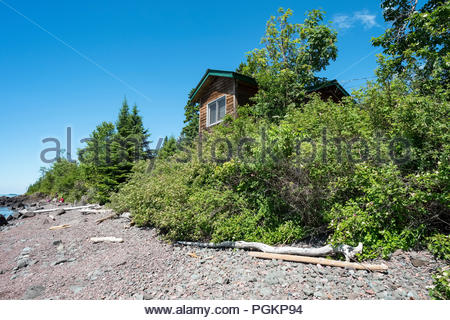 Cabin is perched on a low cliff with sweeping views of Lake Superior, near Grand Marais, Minnesota, USA. - Stock Image