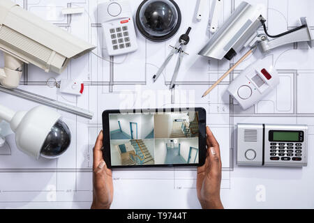 An Elevated View Of Person Watching Footage On Digital Tablet With Security Equipment On Blueprint - Stock Image