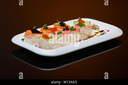 sushi in a plate on a brown background with reflection. fish roll - Stock Image