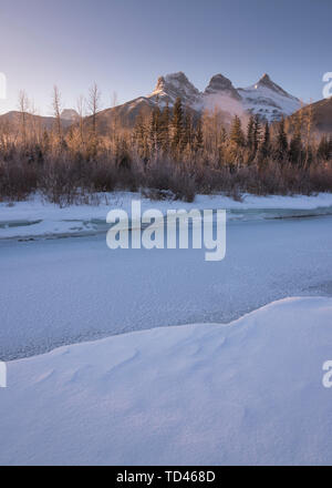 Winter sunrise with frozen Bow River and Three Sisters, Canmore, Alberta, Canadian Rockies, Canada, North America - Stock Image