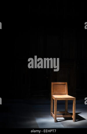 A single wooden chair sits, on a tiled floor, in a shaft of sunlight in Yorkshire's Ampleforth Abbey.  It has - Stock Image