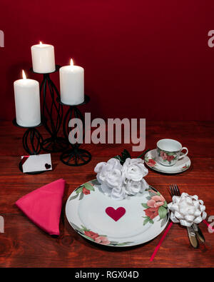 Floral pattern fine china dinnerware with matching plate, cup and saucer. bouquet of white roses, pink napkin, silverware, white candles and card - Stock Image