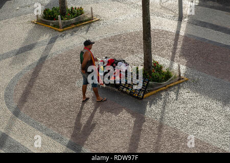 RIO DE JANEIRO, RJ , BRAZIL - December 27, 2018: A street vendor stands in front of his products on sale at the Copacabana Beach sidewalk on a summers - Stock Image