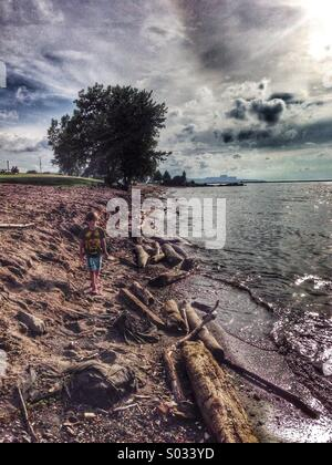 Boy walks along the shore of Lake Erie in Cleveland. - Stock Image