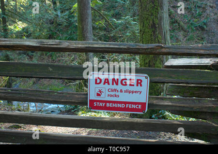 Danger Cliffs & slippery rocks Stay Behind Fence warning sign on a vertical rail fence with trees in behind. - Stock Image