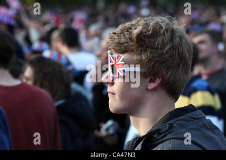 London, UK. June 4, 2012. One fan enjoys the Concert to celebrate The Queen's Diamond Jubilee on the big screens - Stock Image