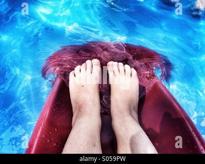 Little girl's feet in pool - Stock Image