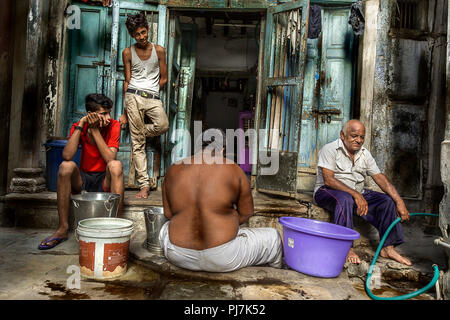 four men waiting for water supply - Stock Image