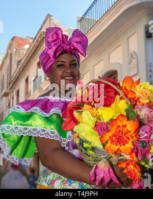 Cuban woman with traditional floral  clothing posing for tourists in street in  Old Havana, Cuba - Stock Image