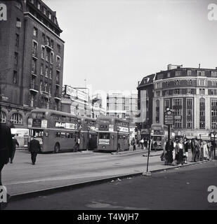 1960s, historical, London routemaster or doubledecker buses parked outside Victoria train station, Victoria, London, England. The tall building seen in the picture is Victoria Station House. - Stock Image