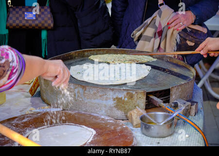 Local woman preparing turkish pancakes (gozleme) . Focus on hot plate and method in Antalya, Turkey - December 29, 2018 - Stock Image