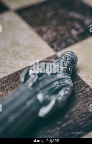 Defeated king chess piece lying on a chessboard - Stock Image