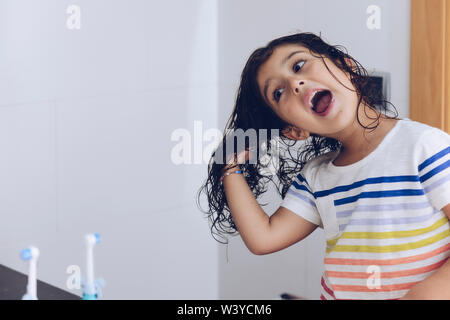 little girl playing with wet hair in front of the mirror after taking a bath, kids hygiene concept, copy space for text - Stock Image