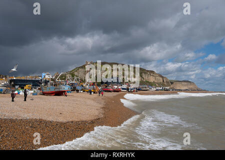 Hastings, East Sussex, UK. 10th March 2019. Hastings fishing boats pulled up high on the Stade beach, protected by the new sea defences and out of reach of the rough sea driven by onshore gales. Hastings has the largest beach-launched commercial fishing fleet in Europe. - Stock Image