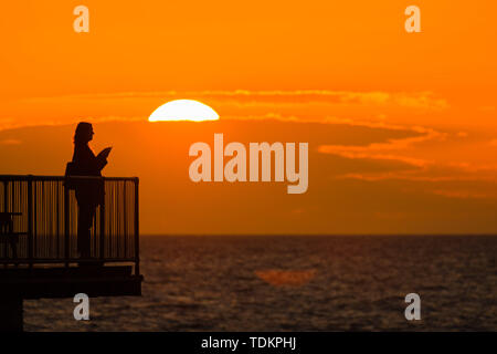Aberystwyth Wales UK, Monday 17 June 2019 UK Weather:After days of heavy rain and grey overcast skies, a fiery sunset over people standing on the pier in Aberystwyth is a reminder of what 'flaming' June weather should be ;like photo Credit: keith morris/Alamy Live News - Stock Image