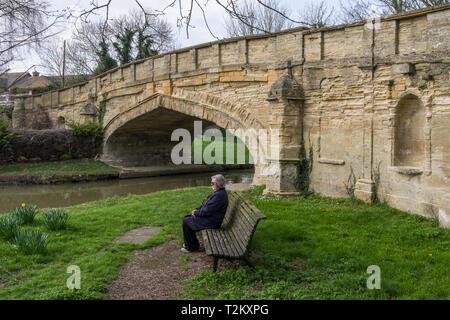 Senior woman sitting on a wooden bench enjoying some Spring sunshine, Cosgrove, Northamptonshire, UK - Stock Image