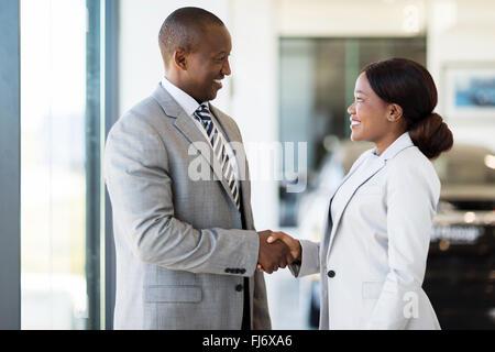 cheerful African car dealer handshake with customer in showroom - Stock Image