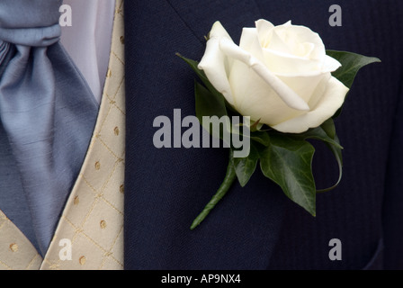 The groom's outfit at a wedding with white rose flower in jacket button hole - Stock Image