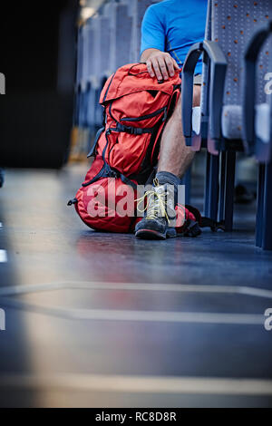 Hiker with rucksack in train - Stock Image