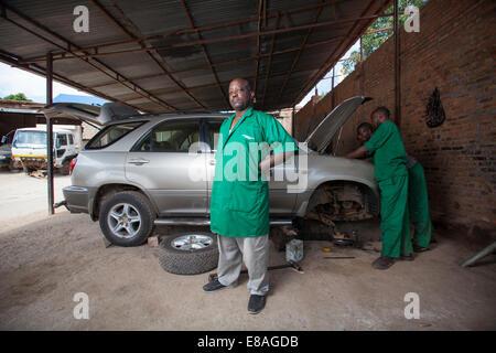 Rwandan mechanic and entrepreneur poses at his garage, Kigali, Rwanda - Stock Image