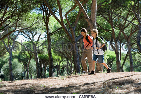 Boy and girl walking in forest - Stock Image