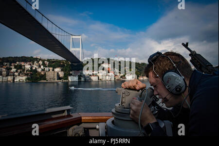 180827-N-UY653-064  BOSPHORUS STRAIT (Aug. 27, 2018) Quartermaster 3rd Class Zach Cicerini stands starboard side bearing taker aboard the Arleigh Burke-class guided-missile destroyer USS Carney (DDG 64) as the ship transits the Bosphorus Strait Aug. 27, 2018. Carney, forward-deployed to Rota, Spain, is on its fifth patrol in the U.S. 6th Fleet area of operations in support of regional allies and partners as well as U.S. national security interests in Europe and Africa. (U.S. Navy photo by Mass Communication Specialist 1st Class Ryan U. Kledzik/Released) - Stock Image