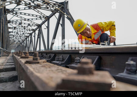 (190423) -- CHONGQING, April 23, 2019 (Xinhua) -- Tang Jinhua checks rails on the previous Baishatuo Yangtze River railway bridge in Jiangjin of southwest China's Chongqing Municipality, April 23, 2019. The previous Baishatuo Yangtze River railway bridge, completed in 1959, will stop service after April 24. All trains will run on the new double decker steel truss cable stay railway bridge after that day. The new bridge has 4 tracks on the upper deck for passenger trains with a designed speed of 200 kilometers per hour and 2 tracks on the lower deck for cargo trains with the designed speed of 1 - Stock Image