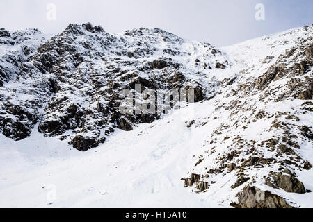 Small snow avalanche runoff in Banana Gully in Cwm Clyd below Y Garn mountain in mountains of Snowdonia National - Stock Image