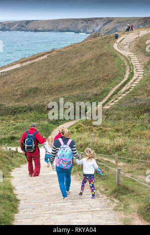 A family of holidaymakers walking down the South West Coast Path to Bedruthan Steps in Cornwall. - Stock Image