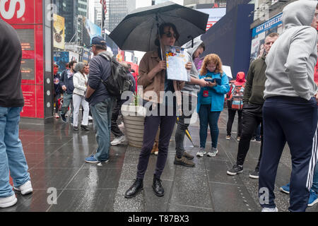 On a rainy Saturday, an attractive young lady selling discount theater tickets to primarily, tourists. Times Square, Manhattan, New York City. - Stock Image