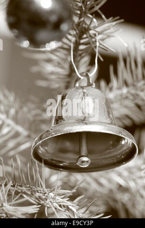 A  bell is hanging on the Christmas tree. Black and white photograph, tinted sepia. - Stock Image