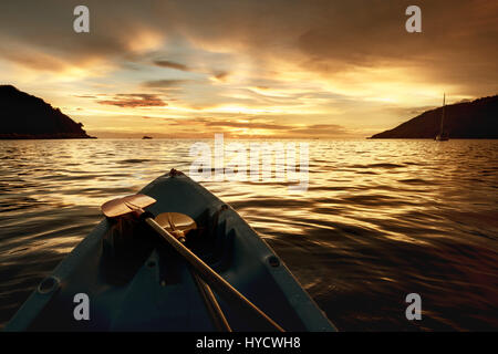 Kayak bow at sunset sea backdrop - Stock Image