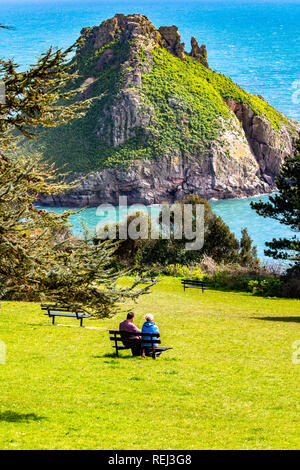 A couple sitting on a bench looking out to sea and the view of Thatcher's Rock in Torbay. - Stock Image
