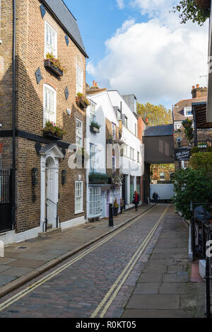 People walking through Perrin's Court, a pretty narrow street of shops, houses, cafes and restaurants, Hampstead, London, England, UK - Stock Image