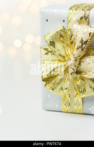 Elegant silver gift box tied with golden ribbon bow bokeh garland lights on white background. Christmas New Years presents holiday magic atmosphere. G - Stock Image
