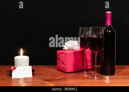 Beautiful etched wine glasses and bottle of red wine, white candle, wrapped present with bow on wooden table with name tag on dark background. - Stock Image