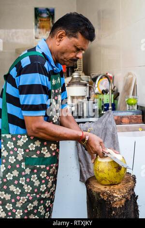 Coconut Vendor Opening a Coconut, Kuala Lumpur, Malaysia. - Stock Image