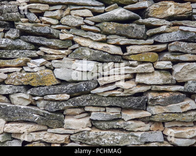 Limestone wall made of dry stacked pieces tiles. Full frame image as background. - Stock Image